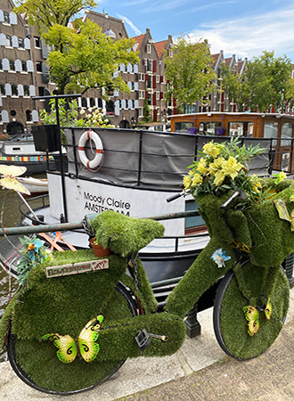 Bicycle with flowers on the canal in Amsterdam