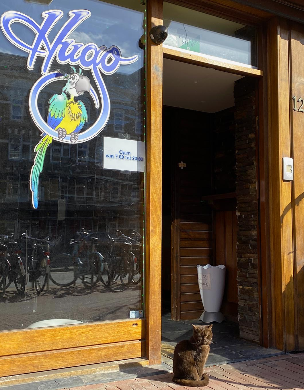 Entrance of the coffeeshop Hugo in Amsterdam and the cat Stoney