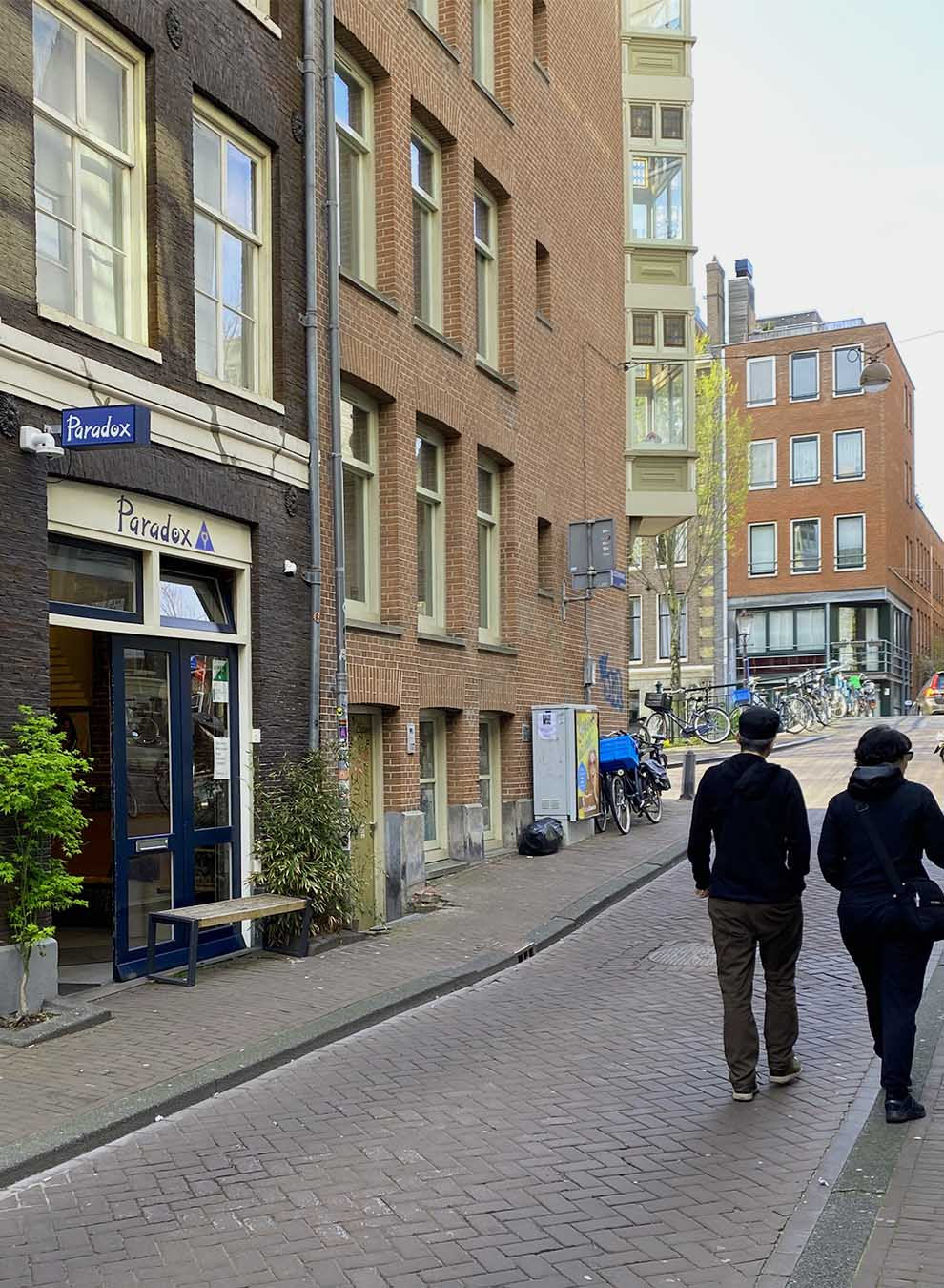 A couple walks on the streets in front of the coffeeshop Paradox in Amsterdam