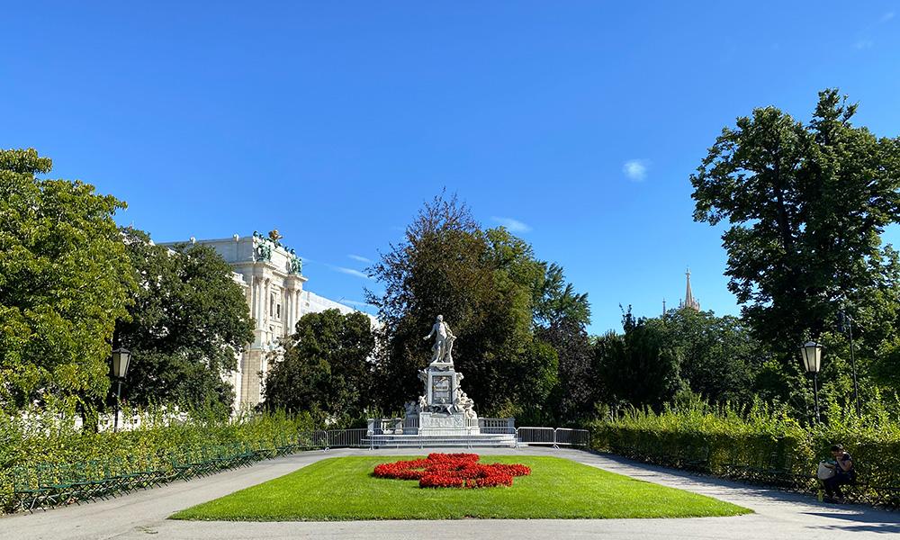 Praça com monumento e jardim em Viena