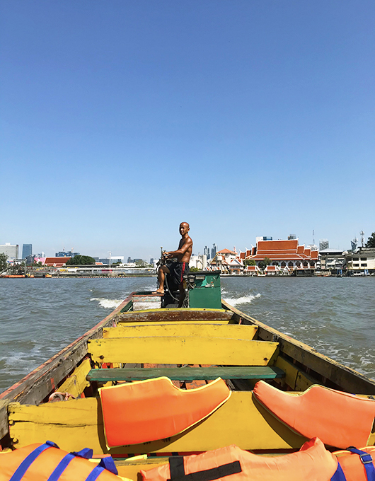 Homem tailandês navega barco sobre o rio Chao Phraya em Bangkok